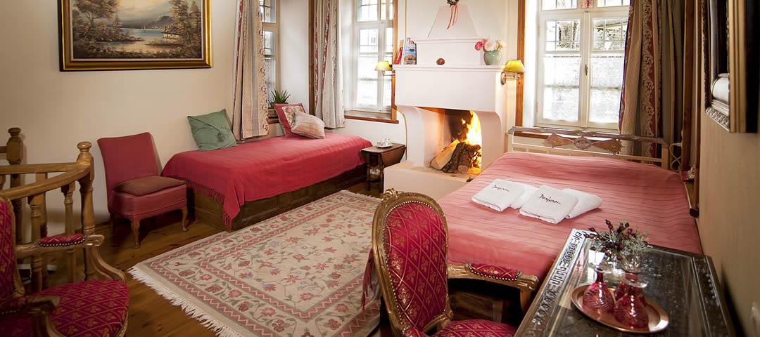 Gamila kamer in het Hotel Porfyron in Zagori is een ruime driepersoonskamer op de begane grond met open haard en een twee- en een eenpersoonsbed