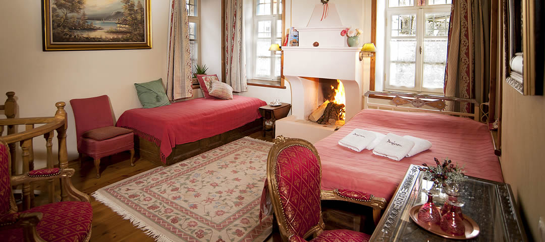 Gamila room in the Hotel Porfyron in Zagori is a spacious triple room on the ground floor of the hotel, with a fireplace and a double and a single bed