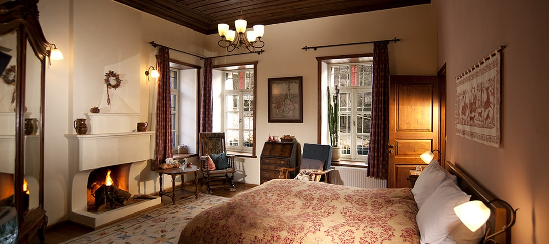 Stouros room at hotel Porfyron in Ano Pedina village, Zagori, is a very spacious double room with a fireplace, a double bed, bathroom with shower, toilet and sink