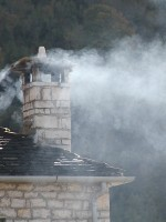 Smoke coming out from a chimney in the stone village of Ano Pedina