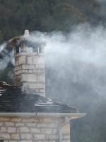 Rook uit een schoorsteen in de steen dorp Ano Pedina, Zagori