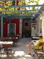 Het lezen van de tijd op de veranda voor een van de gasten van het hotel in Ano Pedina