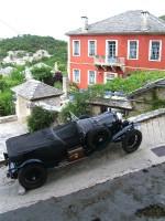 Een vintage auto geparkeerd direct buiten het hotel in Ano Pedina. De bestuurder is genieten van een glas wijn in het restaurant van het hotel
